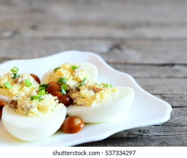 Tasty Deviled Eggs On A Plate And On Old Wooden Background With Copy Space For Text