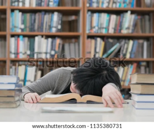 Tired Asian Student Girl With Glasses Sleeping On The Books In The Library