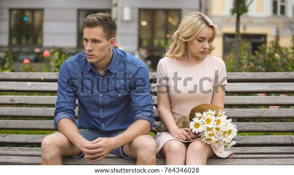 Unhappy couple sitting after fight, girl with flowers, problem in relationship