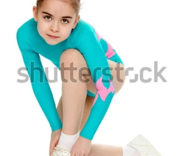 Very Flexible Little Girl Gymnast Junior School Age In A Beautiful Gymnastic Swimsuit Turquoise She Bent Over To Fix The Shoes On Her Leg