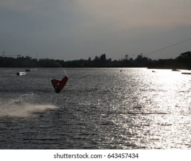 Wake Boarder Doing Half Somersault Creating Plume Of Spray Backlit By Late Afternoon Sun In The