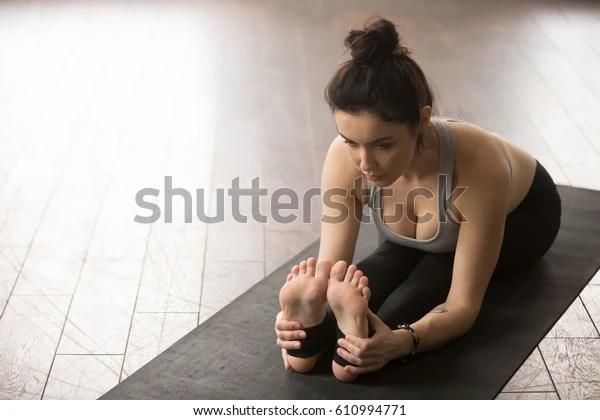 Yogi woman practicing yoga concept, sitting in paschimottanasana exercise, Seated forward bend pose, working out, wearing black sportswear, wooden floor studio background, view from above, copy space