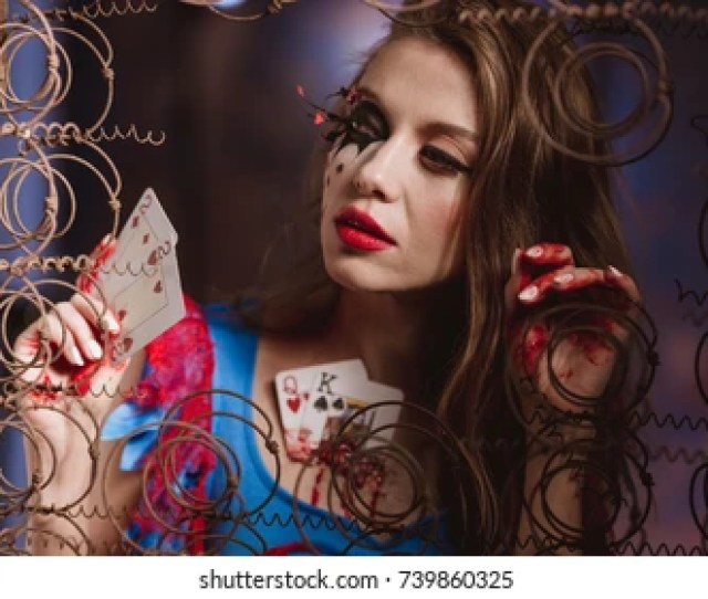 Young Beautiful Woman In A Costume Queen Of Hearts And Make Up Holds Playing Cards