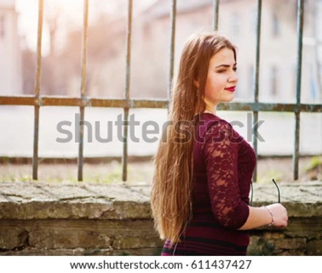 Young Chubby Teenage Girl Wear On Red Dress With Sunglasses At Hand Posed Against Iron Fence