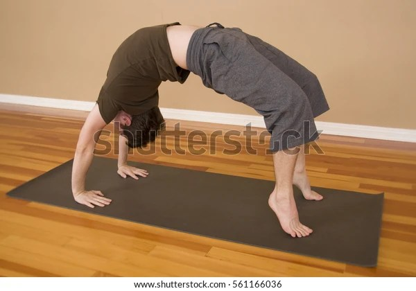 Young Man in Wheel Pose in a Yoga Studio