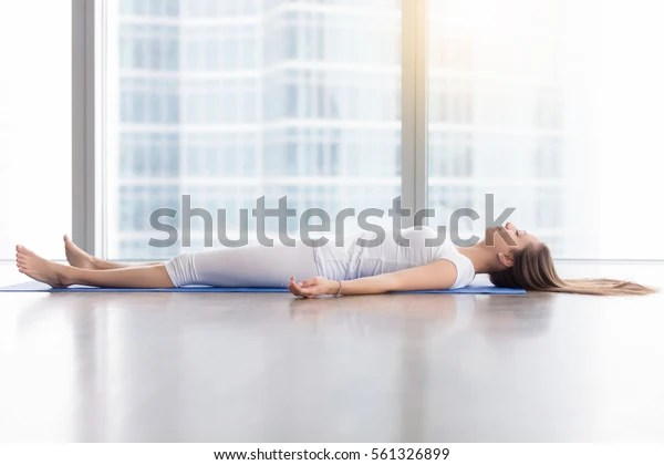 Young woman practicing yoga, lying in Savasana exercise, Dead Body, Corpse pose, working out, wearing sportswear, white t-shirt, pants, indoor full length, near floor window with city view, side view