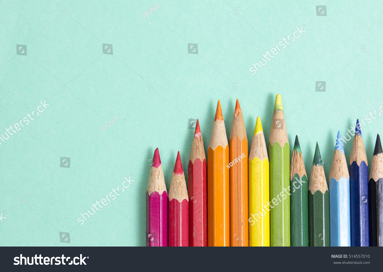 Background Color Pencils On Green Paper Stock Photo
