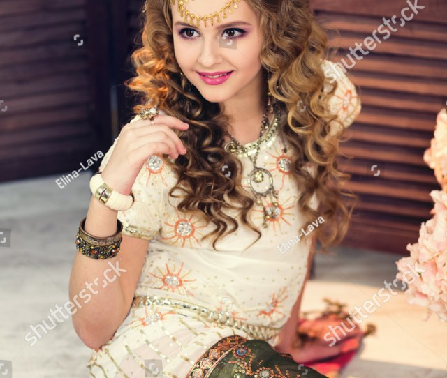 Beautiful Blonde Girl In The White Indian Bright Dress With Oriental Makeup Sitting On The Floor