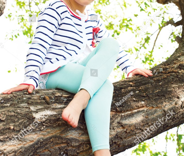 Cute Little Girl Dressed In A Striped Sweater Sitting On A Tree