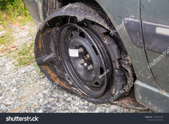 Destroyed blown out tire with exploded, shredded and damaged tire on a modern automobile. damaged truck rubber after tire explosion at high speed. Damaged flat tires: old car.