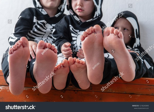 skeleton Happy children in carnival outfits, boys with a red crocodile in the studio. Black suit with the image of skeletons. Classic halloween costume. Funny family kids childhood