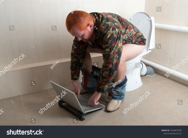 Man with red hair, beard and mustache in a military jacket in glasses with laptop sitting on toilet bowl. Dude is passionate about the information that only he sees and actively expresses his emotions