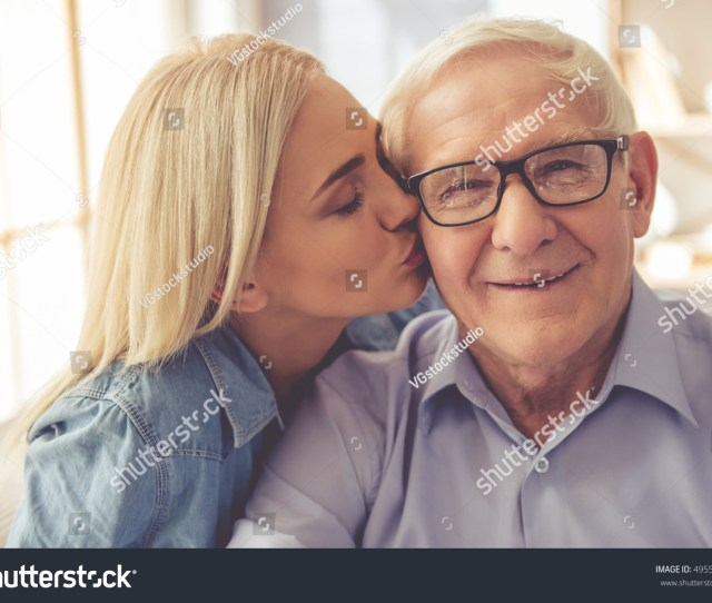 Portrait Of Handsome Old Man And Beautiful Young Girl Girl Is Kissing Her Parent In