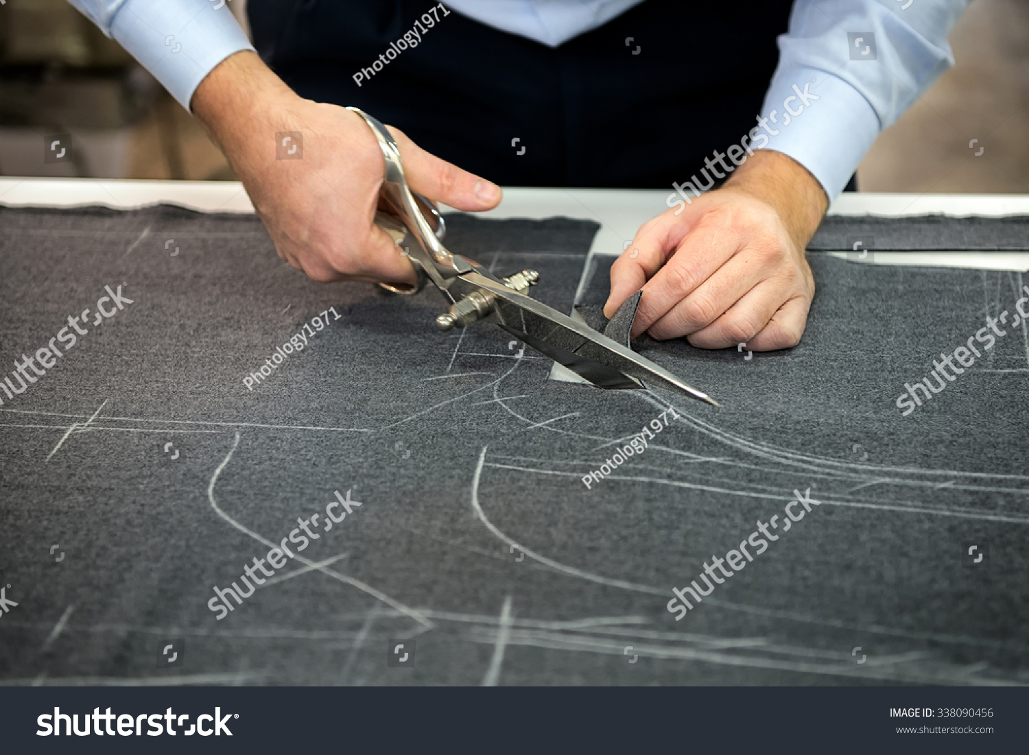 Tailor Cutting Fabric Using Large Scissors Or Shears As He