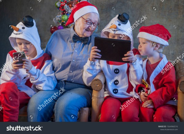 IPhone three brothers in xmas clothes play with tablet and smartphone. Granny sits next to her grandsons and looks at their entertainment. Beautiful elderly woman with gray hair and wrinkles. Kids love mom