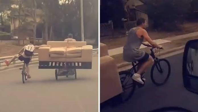 Two Australians carry a sofa through the city on bicycles