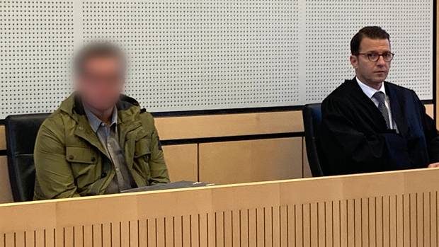 The accused sits in the courtroom next to his lawyer