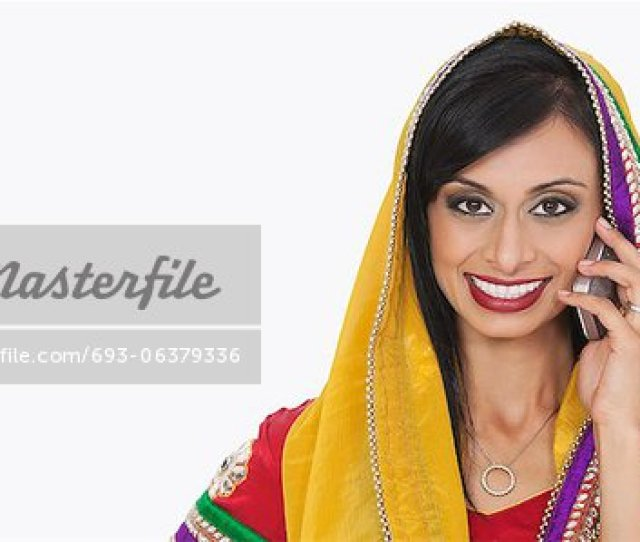 Portrait Of Beautiful Indian Woman In Traditional Wear Answering Phone Call Over White Background Stock Photo