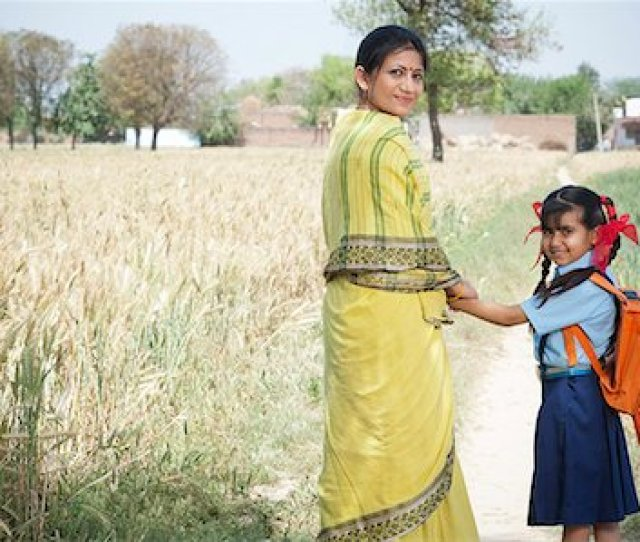 Woman Standing With Her Schoolgirl In The Field Sohna Haryana India Stock Photo