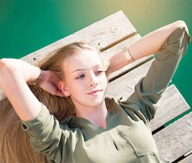 Overhead View Of Young Woman Lying On Wooden Decking Hands Behind Head Looking Away Stock