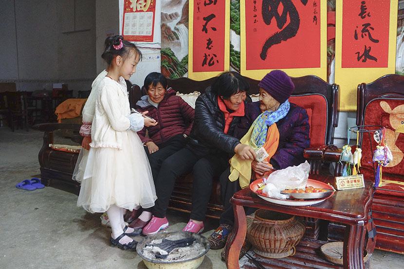 Neighbors offer lunar new year greetings to 112-year-old Huang Ma Kun in Bama County, Guangxi Zhuang Autonomous Region, Jan. 31, 2017. Fan Yiying/Sixth Tone