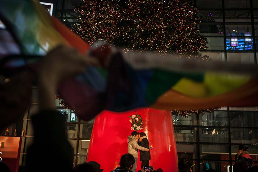 A lesbian couple kiss each other during an event in Shanghai, Dec. 22, 2013. Sun Zhan/Sixth Tone