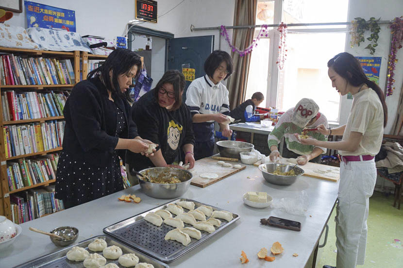 Volunteers make dumplings with the kids at Dalian Children's Village in Liaoning province, April 17, 2017. Fan Yiying/Sixth Tone