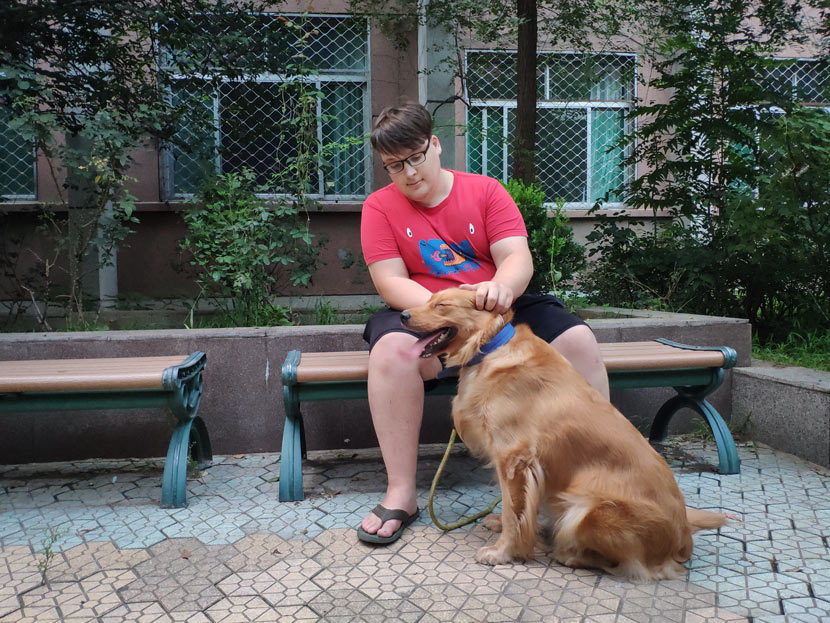 Ken Cari sits on a bench beside his dog, Jenny, in Jinan, Shandong province, Aug. 31, 2018. Fan Yiying/Sixth Tone