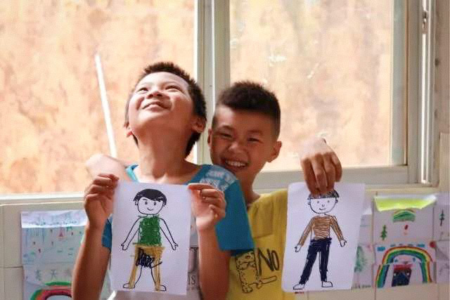 Boys display their drawings during a sex education class at a rural primary school, 2017. Courtesy of You&Me