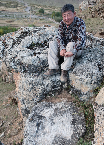 Dr. David Dian Zhang poses for a photo with the ancient hand and foot prints (below) in Tibet Autonomous Region, 2018. Courtesy of David Dian Zhang