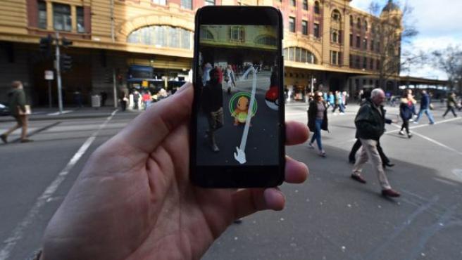 Una persona juega al nuevo Pokemon Go en su móvil, en una calle de Melbourne (Australia). Pokemon Go, con un sistema GPS basado en realidad aumentada, es un juego que está demostrando ser 'enormemente' popular desde que la compañía de desarrollo de software Niantic abrió el acceso a la aplicación el pasado viernes.