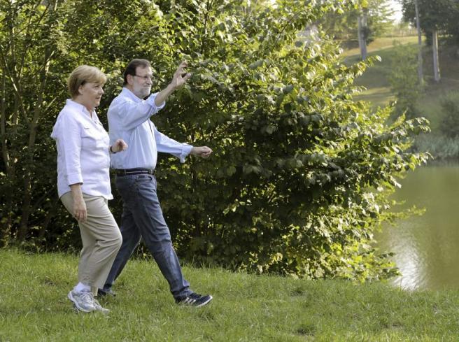 El presidente del gobierno español, Mariano Rajoy conversa con la cancillera alemana Angela Merkel en el castillo de Meseberg (Alemania) en las cercanías de Berlín, al inicio de una cumbre informal.