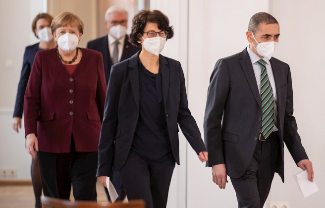 Uğur Şahin y Özlem Türeci, fundadores de BioNTech, entran antes que la canciller Angela Merkel al salón del palacio de Bellevue para el acto de entrega de la Gran Cruz del Mérito.