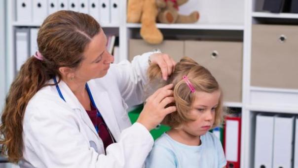 Una doctora revisa el cabello de una niña con piojos.