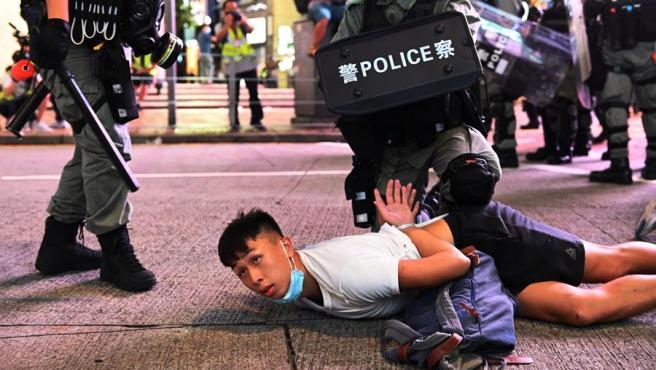 Varios policías detienen a un manifestante durante una protesta contra la nueva ley de seguridad nacional en Hong Kong (China).