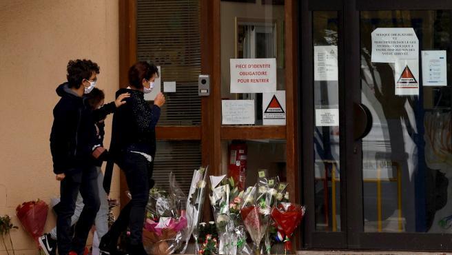 Niños y padres depositan flores frente a la escuela en la que trabajaba como profesor Samuel Paty, decapitado por un extremista islámico.