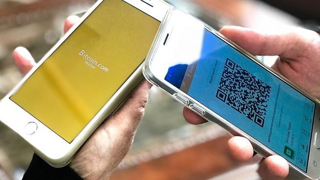 Dos usuarios con carteras de bitcoin en sus móviles.