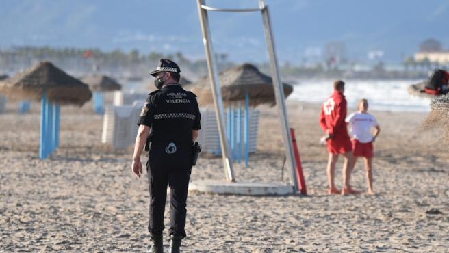 Un agente de la Policía Local y dos socorristas junto al puesto de vigilancia en la playa de la Malvarrosa (Valencia).
