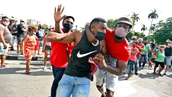 Dos personas detienen a un hombre durante una manifestación contra el Gobierno cubano en La Habana.
