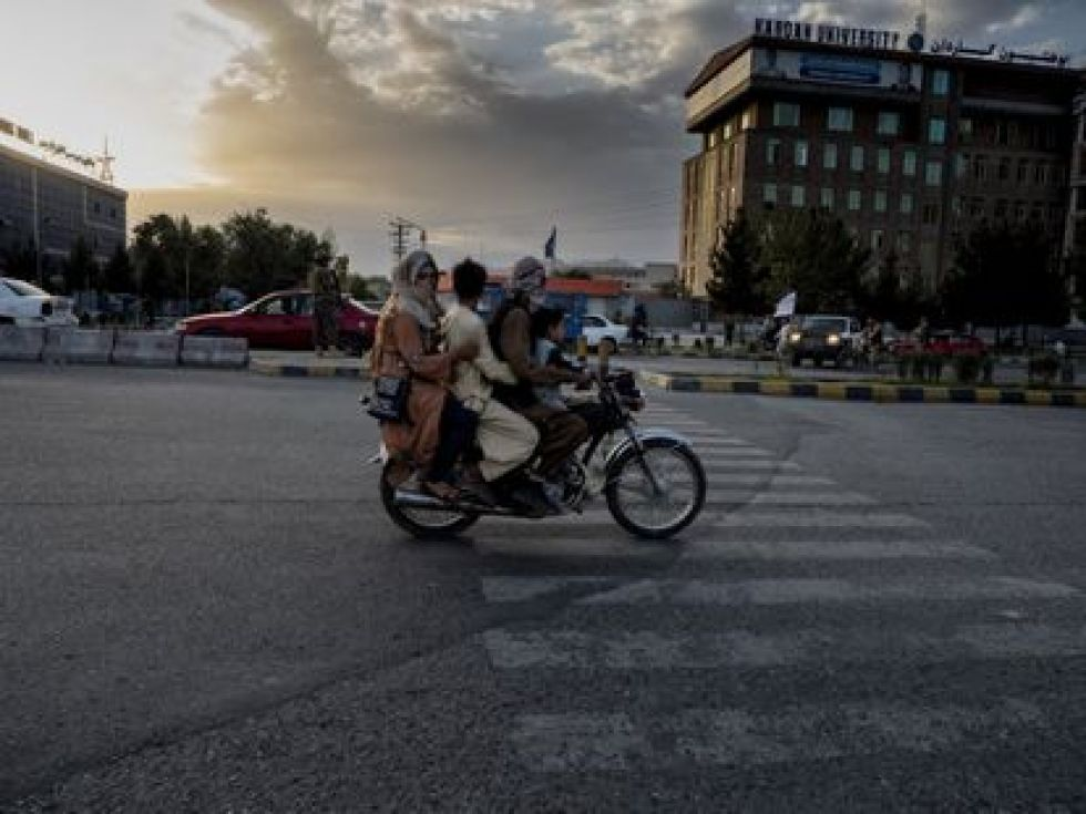 An Afghan family passes a motorcycle on a Kabul street near a fundamentalist checkpoint.
