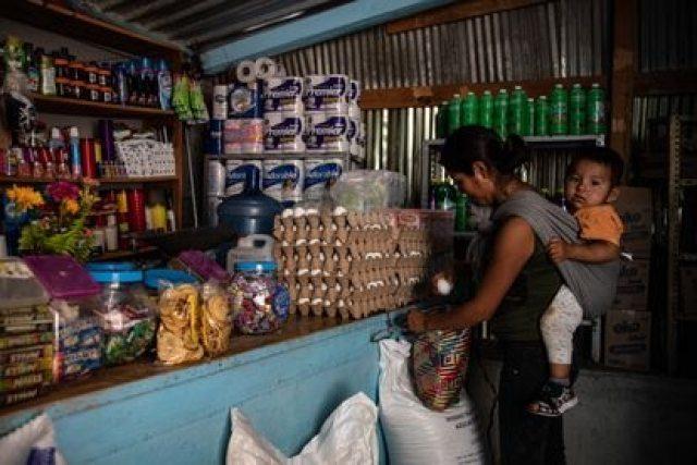 Una mujer y su hijo compran en una tienda de abarrotes en la remota comunidad de Yalálag, en Oaxaca, en agosto de 2020.