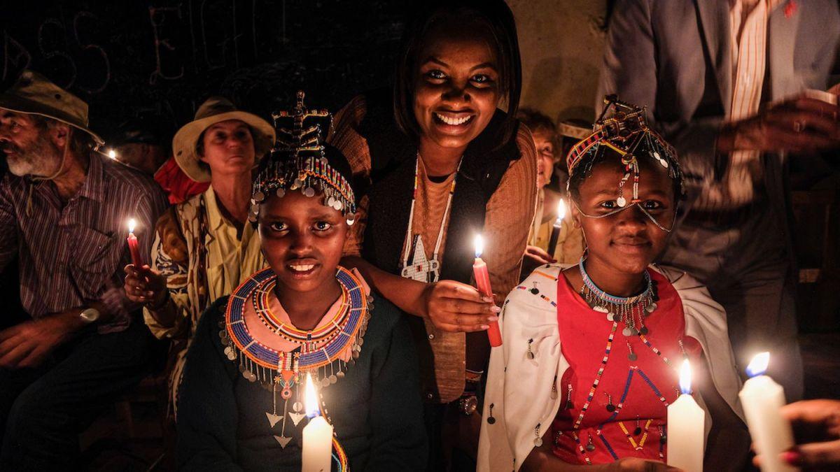 """La ceremonia de la luz es un gesto simbólico que se realiza los días en que se celebran ritos de iniciación alternativos a la ablación con las niñas, los ancianos de la aldea, los hombres masái y, a veces, las instituciones locales. Todos cantan: """"Apaguemos el fuego de la mutilación, encendamos la luz de la educación"""". Condado de Kajiado, Kenia."""