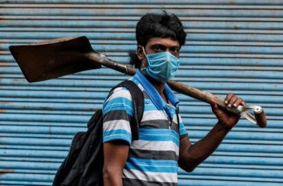 A migrant worker leaves for work after some COVID-19 restrictions were lifted in Kochi, India.