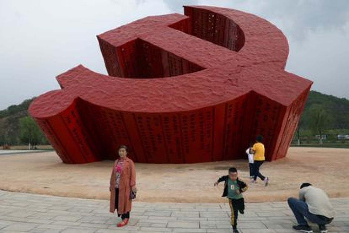 Chinese tourists pose in front of a Communist Party emblem in Nanniwan, a former revolutionary base