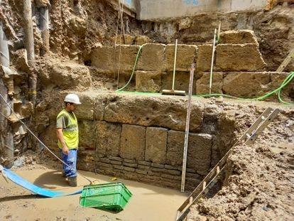 Un obrero, ante la parte exterior de la muralla romana hallada en Sevilla.