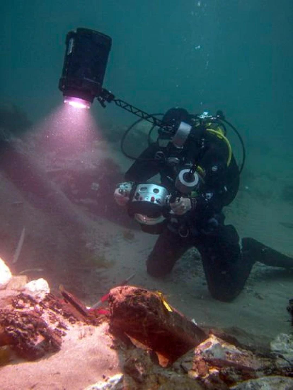 Un arqueólogo graba en alta definición restos de madera del galeón hundido.