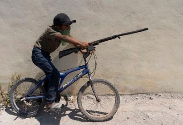 A boy with a simulated weapon rides a bicycle.