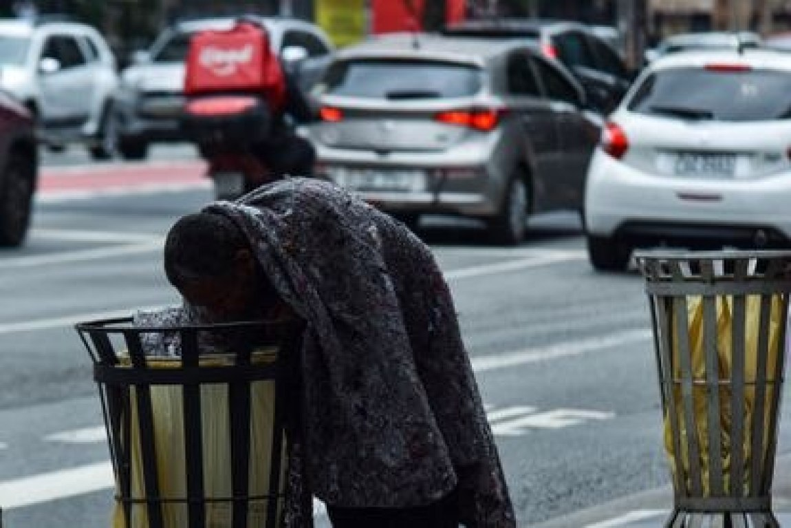 A homeless man searches for food in a trash can on São Paulo's Avenida Paulista on June 29.