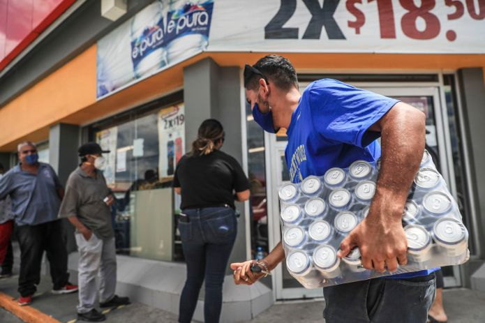 A man with a pack of beers outside a commercial establishment in Mexico.