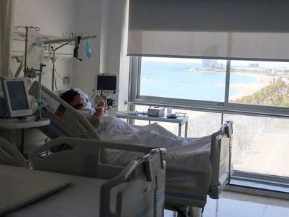 Un paciente con covid mira el móvil en una habitación del Hospital del Mar de Barcelona